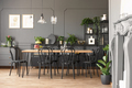 Lamps above wooden table and black chairs in grey dining room in - PhotoDune Item for Sale