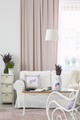 Flowers on table near white couch and armchair in feminine pink - PhotoDune Item for Sale