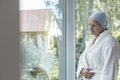 Lonely woman with cancer standing next to a window - PhotoDune Item for Sale