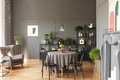 Black chairs at round table under lamp in grey loft interior wit - PhotoDune Item for Sale