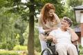 A female volunteer helping an elderly woman in a wheelchair in t - PhotoDune Item for Sale