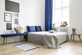 Bedroom design in modern apartment. Bed with dark blue pillows a - PhotoDune Item for Sale