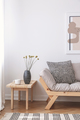 Flowers on wooden table next to beige couch with cushion in flat - PhotoDune Item for Sale