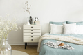 A bright bedroom interior with sage green and white bedding, pil - PhotoDune Item for Sale