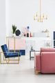 Vertical view of pink velvet couch and blue armchair in living r - PhotoDune Item for Sale