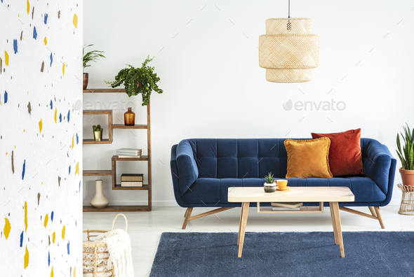 Lamp above wooden table in front of blue sofa with cushions in c - Stock Photo - Images