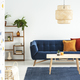 Lamp above wooden table in front of blue sofa with cushions in c - PhotoDune Item for Sale