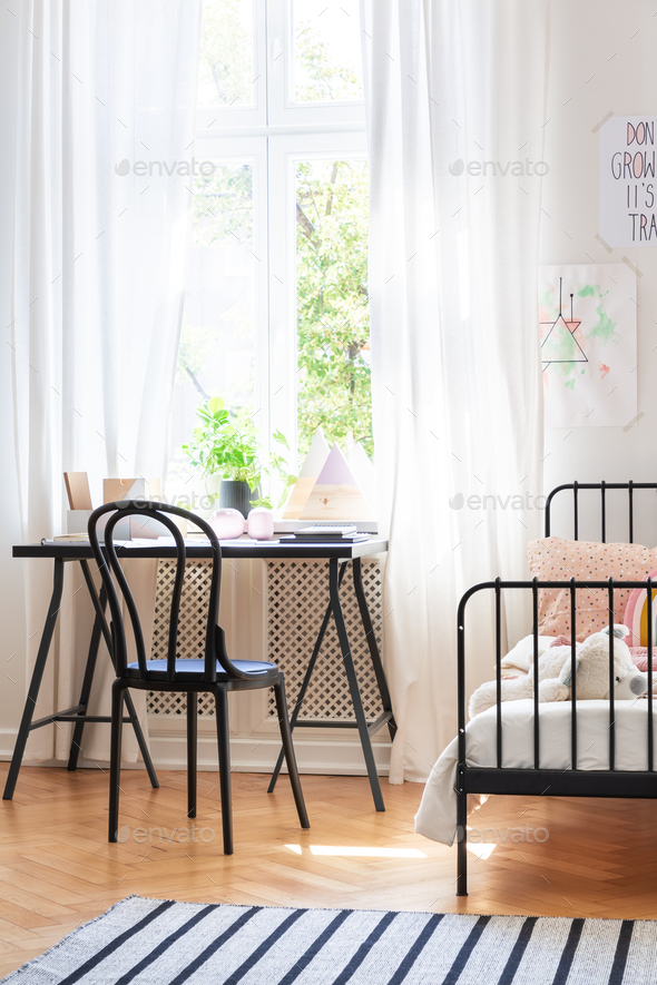 Black chair at desk next to bed in teenager's room interior with - Stock Photo - Images