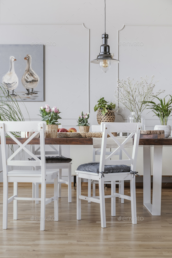White chairs at wooden table in cottage dining room interior wit - Stock Photo - Images