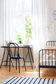 Black chair at desk next to bed in teenager's room interior with - PhotoDune Item for Sale