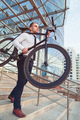 Handsome young businessman in a white shirt and black tie carries his bike - PhotoDune Item for Sale
