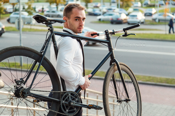 Handsome young businessman in a white shirt and black tie carries his bike - Stock Photo - Images