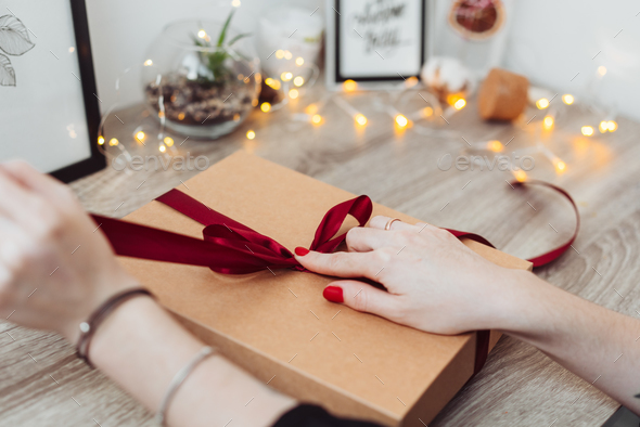 Woman wrapping present in paper with red ribbon - Stock Photo - Images