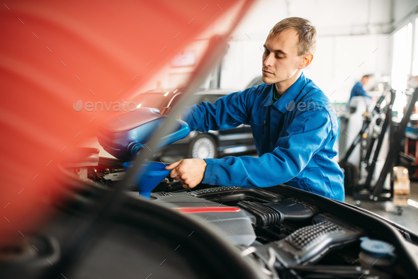 Technician pours new oil into the car engine - Stock Photo - Images