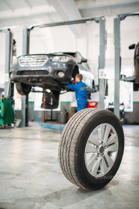 Wheel on the floor in tire service, car on lift - Stock Photo - Images