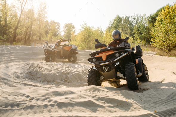Two atv riders in helmets ride in a circle on sand - Stock Photo - Images