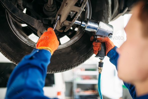 Technician with a wrench repair car suspension - Stock Photo - Images