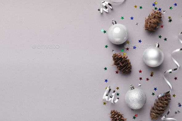 Christmas balls and pine cones on grey background - Stock Photo - Images