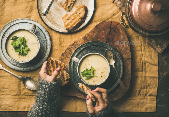 Celery cream soup and female hands with grilled bread - Stock Photo - Images