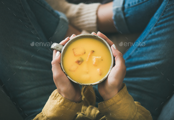 Female keeping mug of pumpkin yellow cream soup in hands - Stock Photo - Images