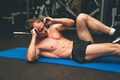 Muscular man on floor working out on abdominal muscles. - PhotoDune Item for Sale