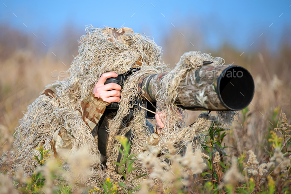 Wildlife photographer in the ghillie suit working - Stock Photo - Images