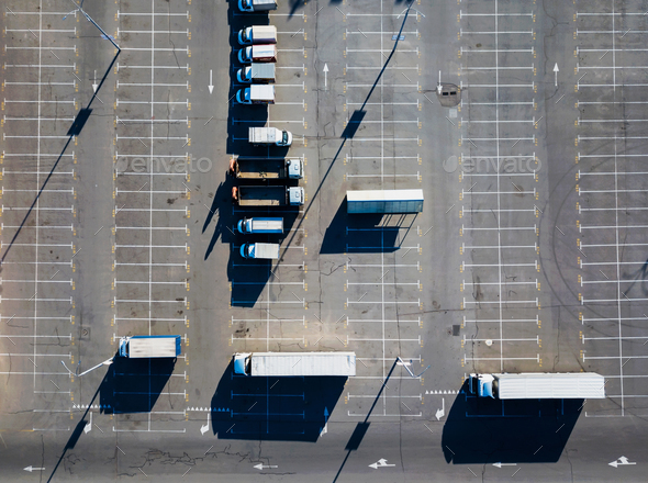 Aerial view from a drone of a parking lot with a multitude of trucks on a sunny day. Top view - Stock Photo - Images