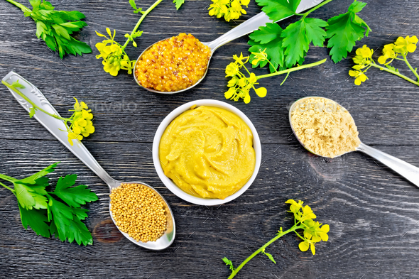 Mustard different in bowl and spoons on black board top - Stock Photo - Images
