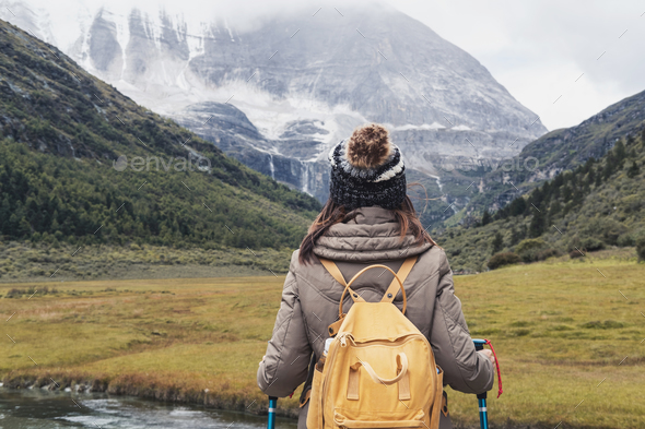 Hiking young woman traveler with backpack looking beautiful landscape - Stock Photo - Images