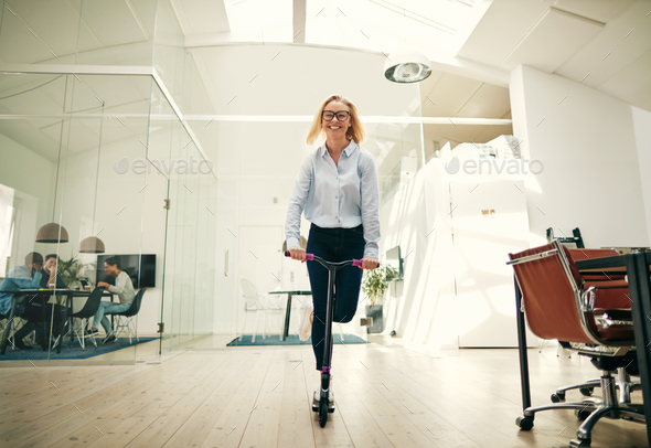 Young businesswoman laughing while riding a scooter around her office - Stock Photo - Images