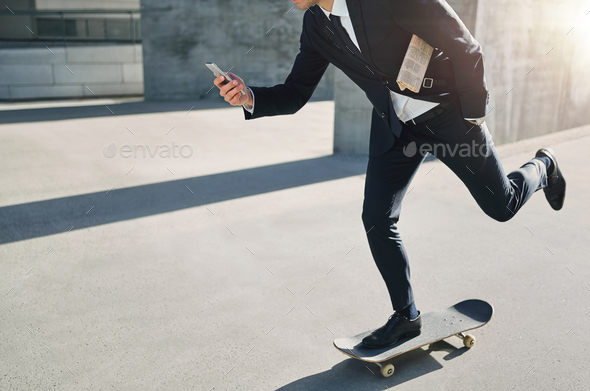 Businessman on a skateboard checking his phone - Stock Photo - Images