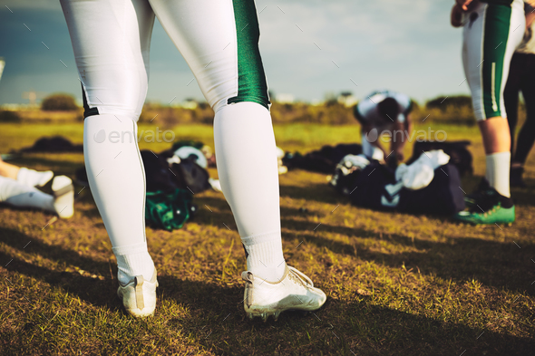 Closeup of football players on a field with their equipment - Stock Photo - Images