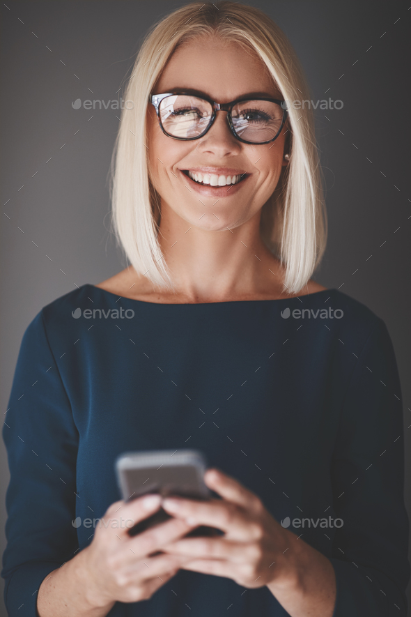 Smiling businesswoman using her cellphone against a gray background - Stock Photo - Images