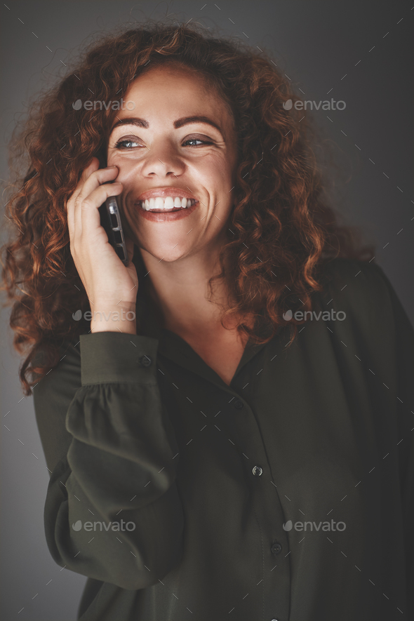 Young businesswoman talking on her cellphone against a gray background - Stock Photo - Images