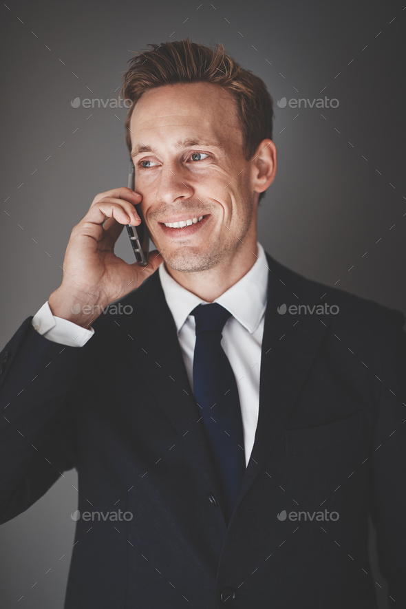 Smiling businessman talking on his cellphone against a gray background - Stock Photo - Images