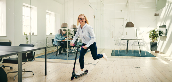 Laughing young businesswoman riding a scooter in a large office - Stock Photo - Images