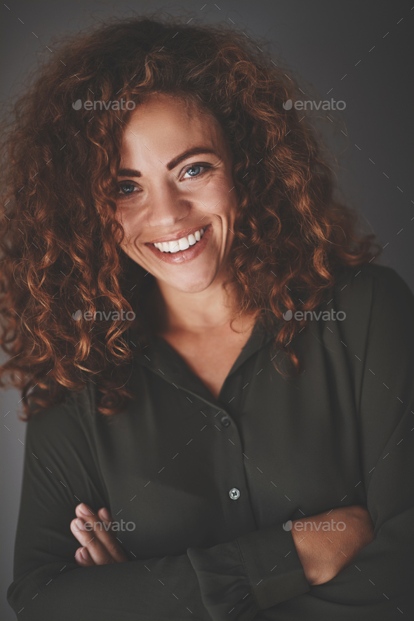 Young businesswoman smiling confidently while standing against a gray background - Stock Photo - Images