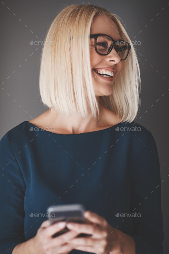 Laughing young businesswoman standing against a gray background reading texts - Stock Photo - Images