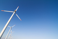 angled view of wind turbines against a blue sky - PhotoDune Item for Sale