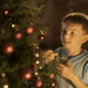 Cheerful boy decorating his Christmas tree at home - PhotoDune Item for Sale