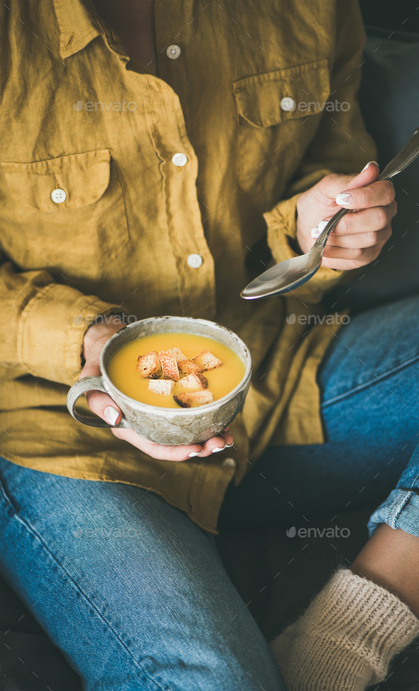 Woman sitting and eating yellow warming pumpkin soup in mug - Stock Photo - Images