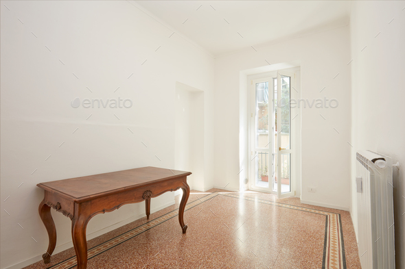White room with wooden table in renovated apartment - Stock Photo - Images