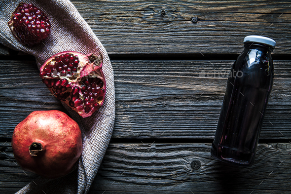 Pomegranate and bottles of essence or tincture on wooden rustic table - Stock Photo - Images