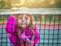 Girl looking through the tennis net - PhotoDune Item for Sale