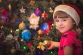 Cute happy girl decorating Christmas tree - PhotoDune Item for Sale