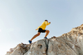 man in sports clothes climbing steep mountain - PhotoDune Item for Sale