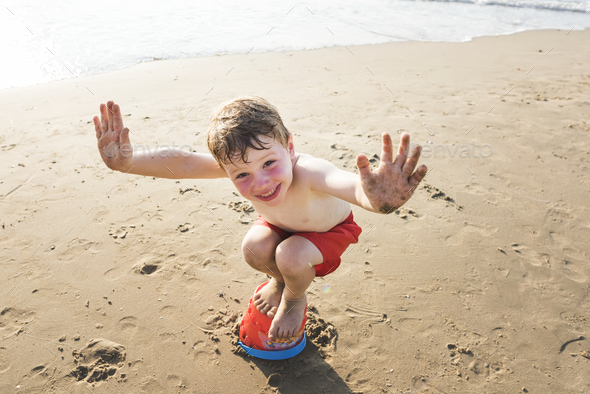 Little kid playing at the beach - Stock Photo - Images