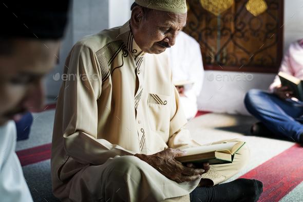 Muslim men reading Quran during Ramadan - Stock Photo - Images
