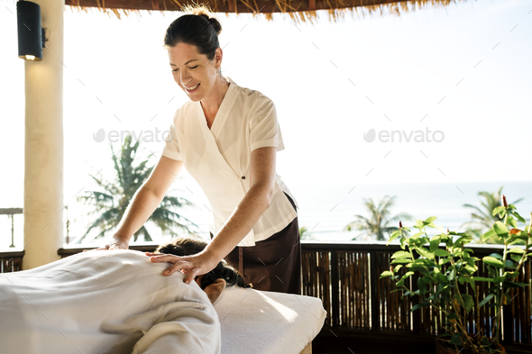 Female massage therapist giving a massage at a spa - Stock Photo - Images