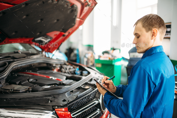 Technician fills check list, car with opened hood - Stock Photo - Images